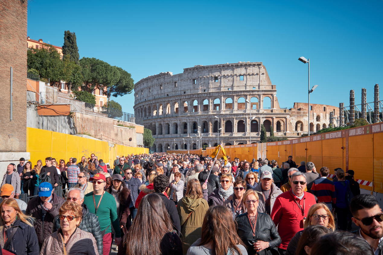 Tourists walk by the famous Colosseum on a sunny day.