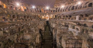 A night photography of the interior of the Colosseum clearly showing the underfloor tunnels