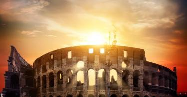 Ancient roman colosseum and sunny sunrise in Rome, Italy
