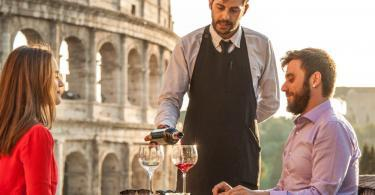 Elegant waiter serving red wine to a young happy couple in bar restaurant in front of colosseum in rome at sunset