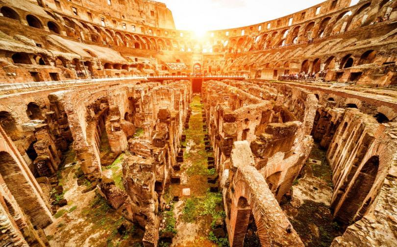 Inside the Colosseum or Coliseum in summer, Italy. Colosseum is the main travel attraction of Roma. Ruins of the Colosseum arena. Panoramic view of Colosseum in the sunlight.