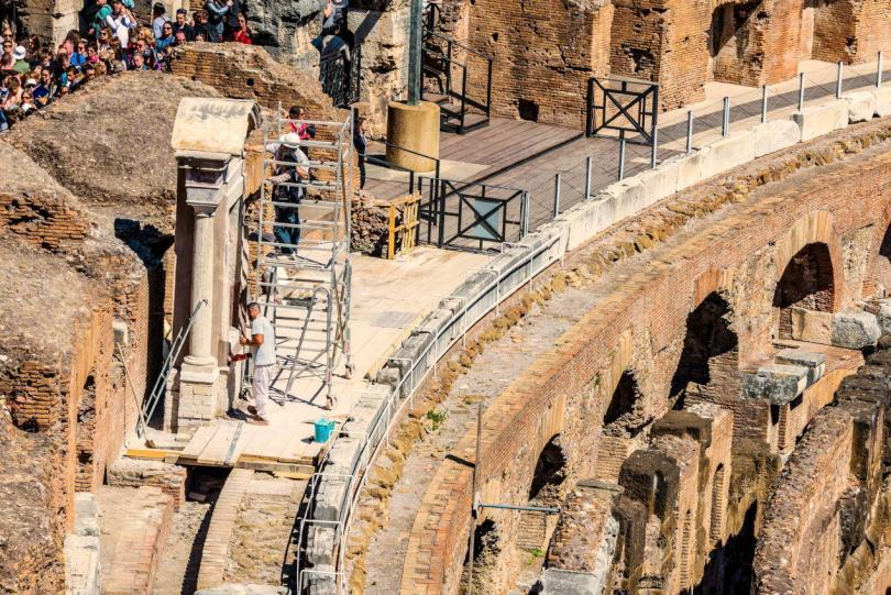 Inside view of The Colosseum with tourists sightseeing.
