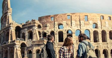 Three young friends tourists standing in front of colosseum in rome with backpacks sunglasses happy beautiful girl long hair. Lens flare.