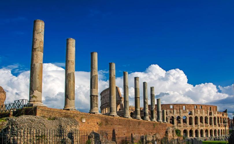 beautiful view of Colosseum with ancient columns on blue sky background with dramatic white clouds. view from Via Sacra, Rome, Italy