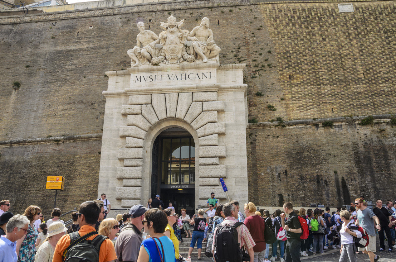 Long lines of tourists and believers outside the entrance of Vatican City, walls of Vatican, Rome