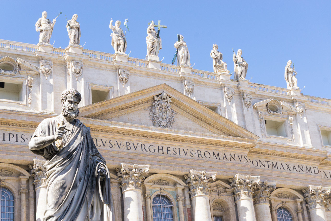 Statue of Saint Peter and Saint Peter's Basilica at background in St. Peter's Square, low angle shot, Vatican City, Rome, Italy