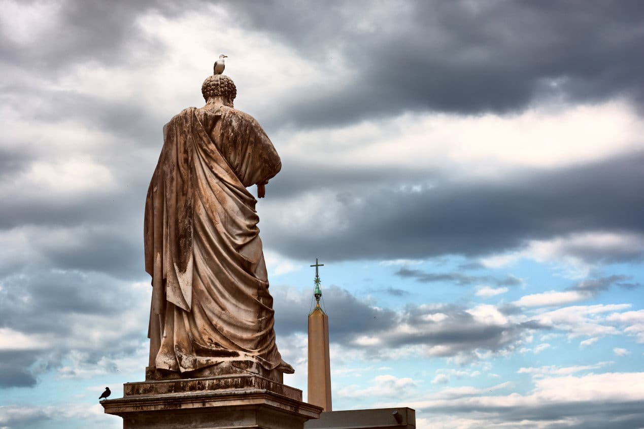 The back of the Saint Peter statue and the obelisk outside the Papal Basilica of Saint Peter