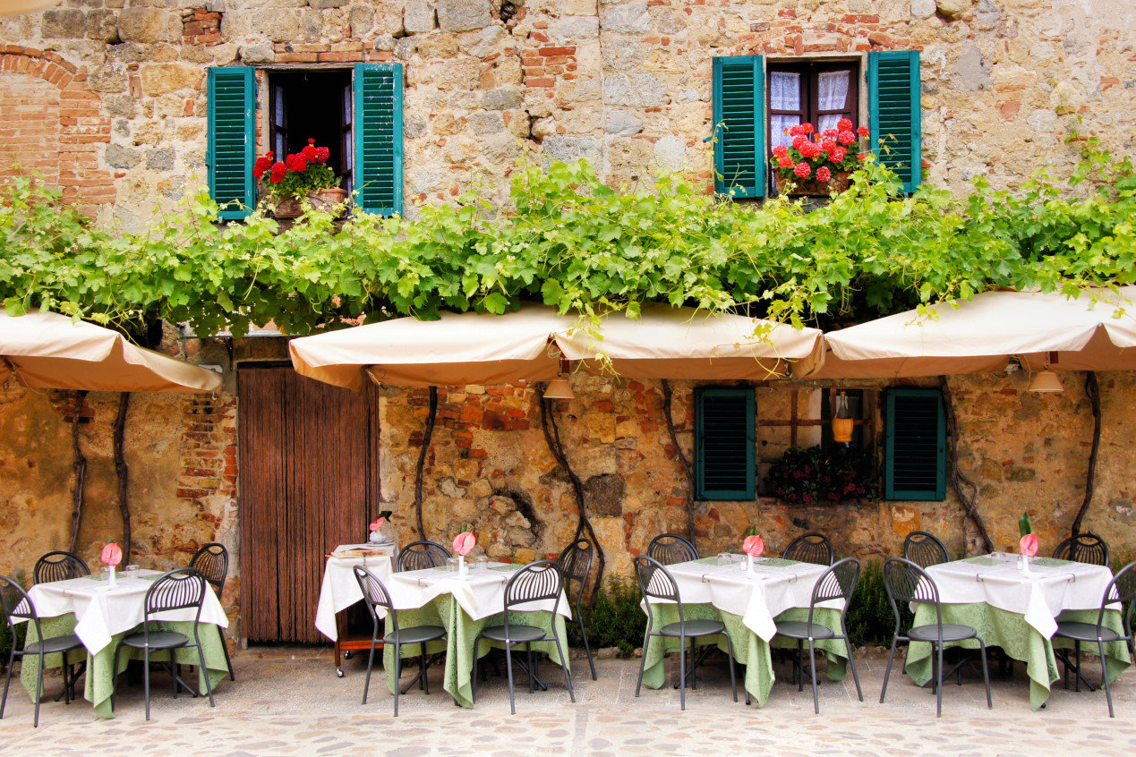 Things to do in Tuscany - Cafe tables and chairs outside a quaint stone building in Tuscany, Italy