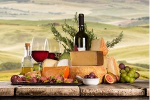 Things to do in Tuscany- Delicious cheeses with red wine on wooden table. Italian countryside, Tuscany.