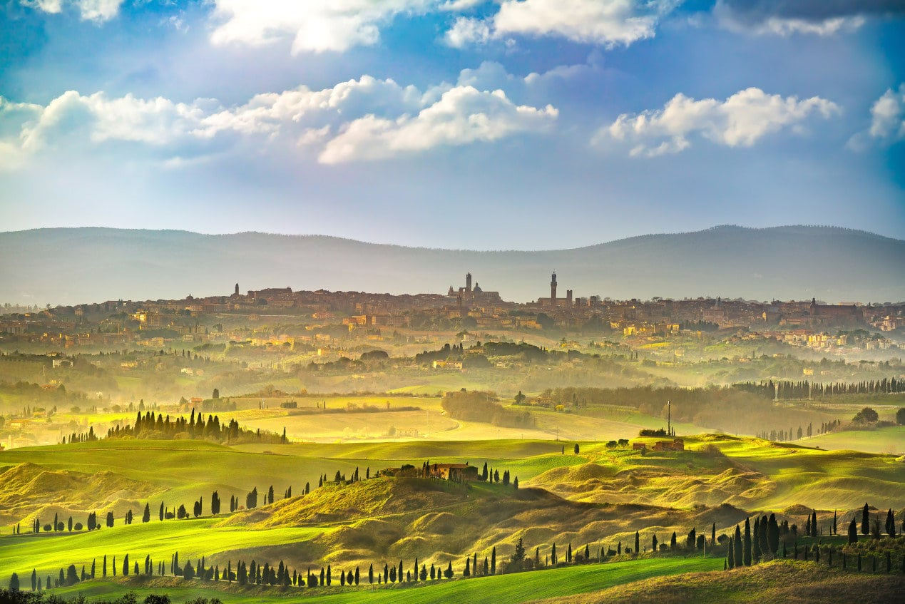 Things to do in Tuscany - Siena city panoramic skyline, countryside and rolling hills in a misty day. Tuscany, Italy, Europe.