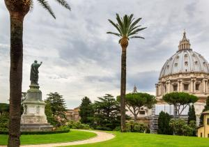 View at St Peter's Basilica (Basilica di San Pietro) from Vatican Gardens with beautiful green lawns, palm trees and paths, Rome, Italy.