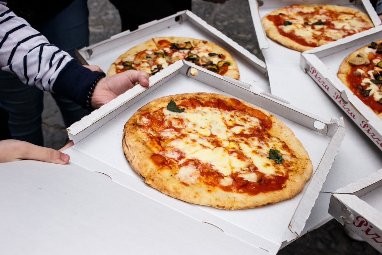 pizza Margarita in the box at the street, woman`s hands closeup, Naples, Italy