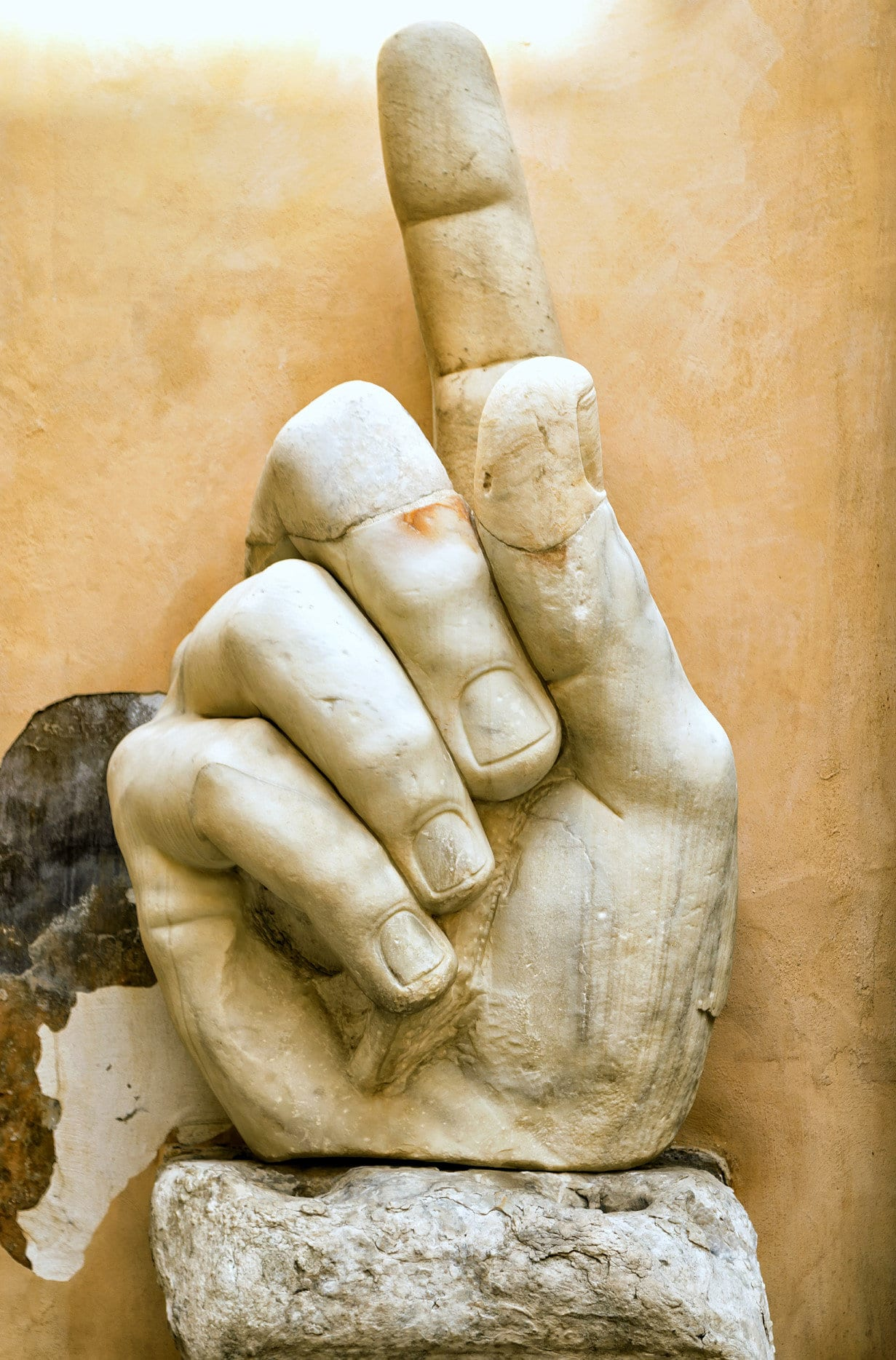 Fragment of a giant statue of Constantine the Great at the Capitoline Hill. Stone hand with raised index finger of Constantine's colossus in Capitoline museum outdoor.