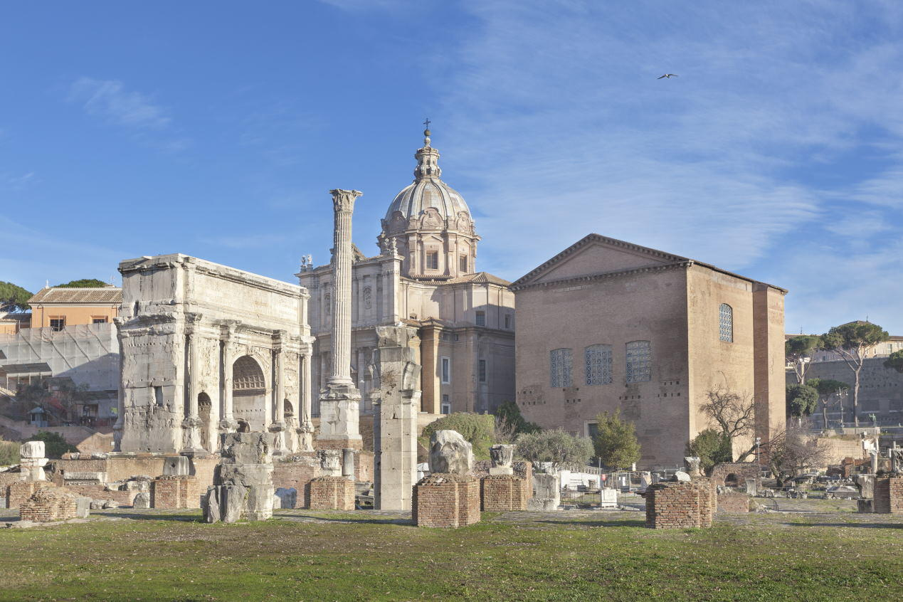 Roman ruins with Curia and Triumphal Arch of Septimius Severus on Roman forum in Rome, Italy