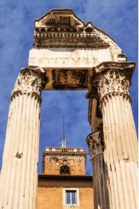 The Tabularium building peeking through the columns of the Temple of Vespasian and Titus, Roman Forum, Italy