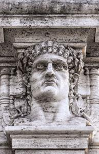 A statue relief of emperor Nero's head on the gateway entrance to the park that contains the ruins of his golden palace at domus aurea in Rome.