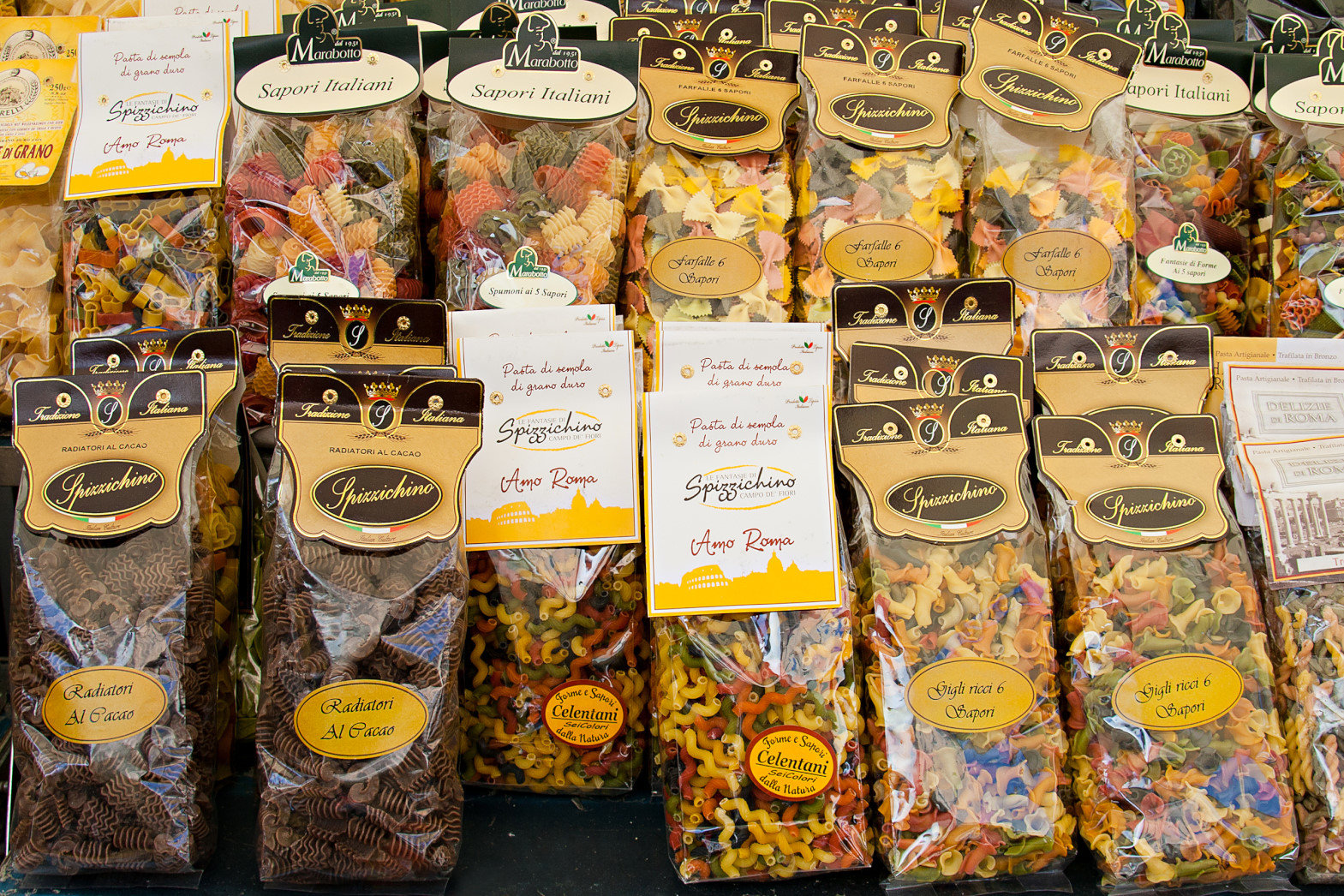 Packaging with colorful and brown pasta on the market Campo dei Fiori.