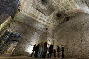 People exploring antique roman ruins being restored - domus aurea
