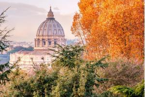St Peter's basilica in Vatican, Rome (Italy), seen through the autumn trees of Gianicolo (janiculum) hill at sunset