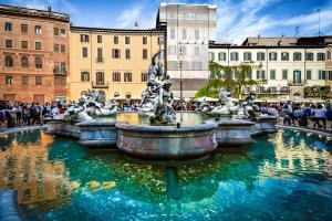 Tourists crowd around the The baroque Fontana del Moro or Moor Fountain in the Piazza Navona in Rome Italy