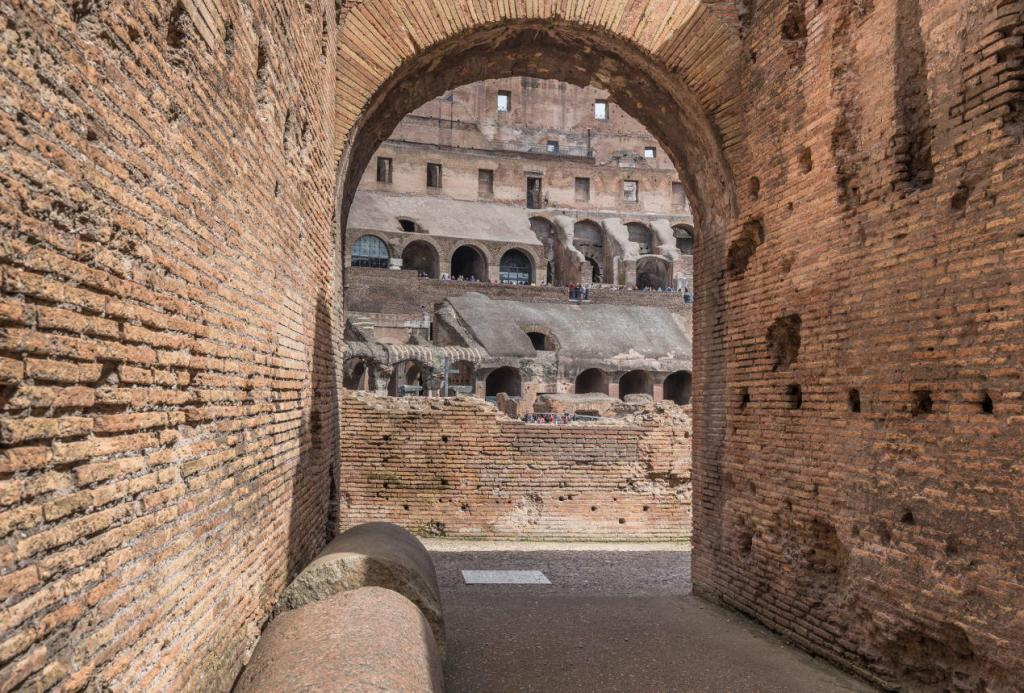 Colosseum & Roman Forum and Palatine Package- Arched entrance (80 in total) into the largest oval amphitheater built by the Flavian dynasty, an iconic majestic symbol of Imperial Rome
