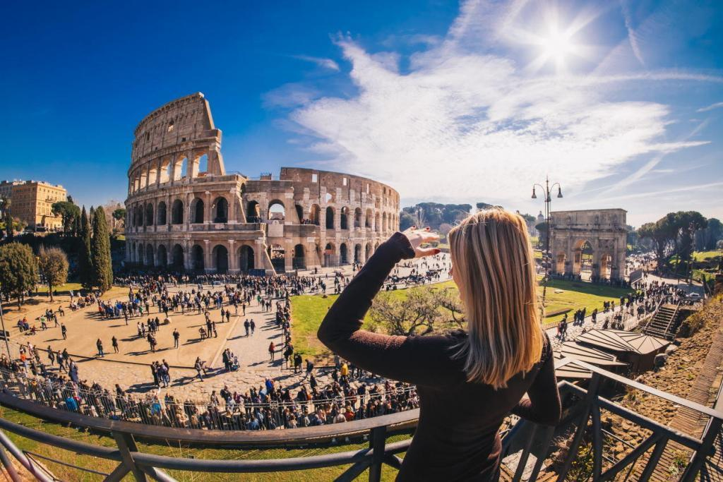 Colosseum & Roman Forum and Palatine Package - Woman tourist enjoying the view of the Roman Colosseum in Rome, Italy