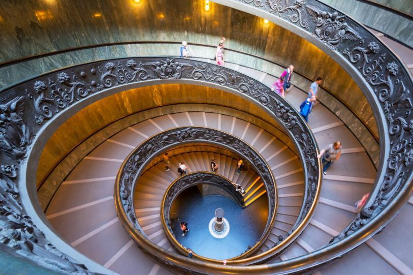 Double spiral stairs in the Vatican Museums, Rome, Italy. View of the old spiral staircase from above. Tourists descend the beautiful spiral stairs.